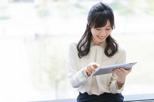 タブレットPCを見て微笑むビジネス女性の写真素材 [FYI02971414]
