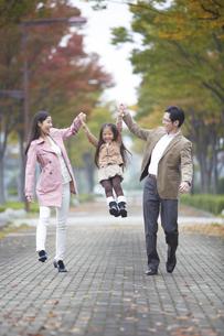 遊歩道で女の子を高く上げて笑い合う家族の写真素材 [FYI02971416]