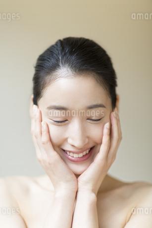 頬に両手を添えた笑顔の女性の写真素材 [FYI02971423]