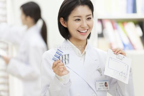 薬の説明をする女性薬剤師の写真素材 [FYI02971425]