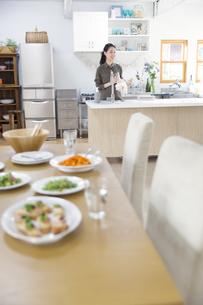 キッチンでコップを拭く女性の写真素材 [FYI02971428]