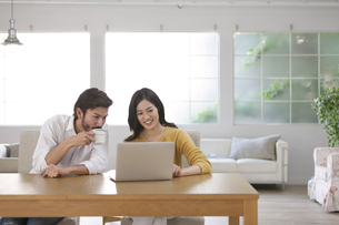 椅子に座ってパソコンを見る男性と女性の写真素材 [FYI02971436]