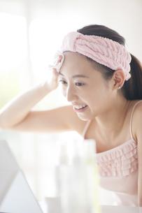 鏡の前で頬にコットンをあてスキンケアをする女性の写真素材 [FYI02971449]