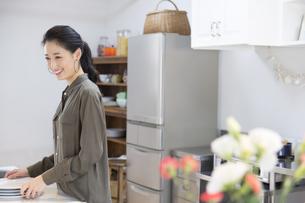 キッチンで食器の準備をする女性の横顔の写真素材 [FYI02971450]