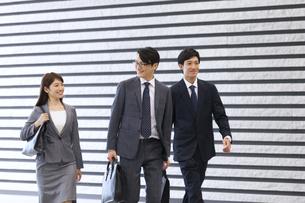 オフィスビルのロビーを歩くビジネス男女の写真素材 [FYI02971461]
