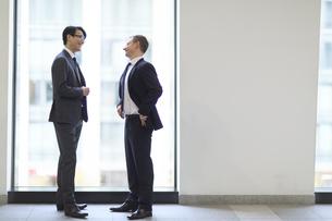 窓際で向かい合って会話をするビジネス男性の写真素材 [FYI02971464]