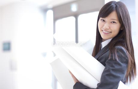 封筒と筒を持って微笑むビジネス女性の写真素材 [FYI02971471]