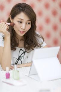 鏡の前でメイクアップをする女性の写真素材 [FYI02971484]