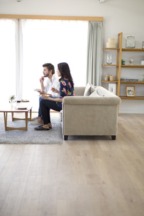 ソファーに座って食事をする男性と女性の横顔の写真素材 [FYI02971486]