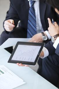 タブレットPCを持ち打ち合せをするビジネス男性の手元の写真素材 [FYI02971488]