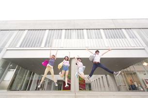 建物の前でジャンプする学生たちの写真素材 [FYI02971489]