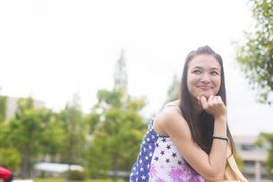 顎に手をあてて微笑む女子学生の写真素材 [FYI02971492]
