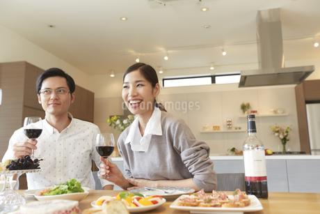 ホームパーティでワインを手に笑う男女二人の写真素材 [FYI02971499]