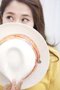 帽子で顔を隠して上を見上げている女性の写真素材 [FYI02971501]