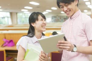 スマートデバイスを見る男女の学生の写真素材 [FYI02971503]