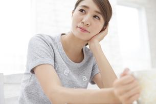 頬に手をあて上を見上げる女性の写真素材 [FYI02971511]