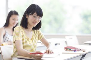 授業でノートを見る女子学生の写真素材 [FYI02971512]