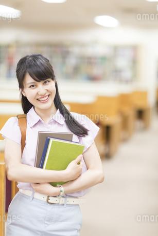 図書室で本を抱える女子学生のポートレートの写真素材 [FYI02971516]