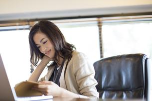 オフィスのデスクで本を読むビジネス女性の写真素材 [FYI02971532]
