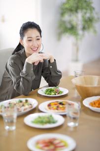 ダイニングテーブルで椅子に座って微笑む女性の写真素材 [FYI02971541]