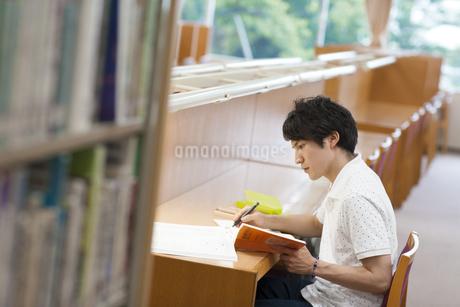 図書室で勉強する男子学生の写真素材 [FYI02971548]