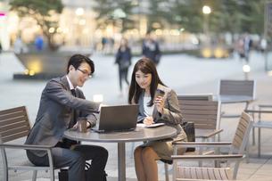 街中で会話しながらノートPCを操作する男女の写真素材 [FYI02971559]