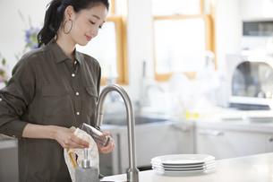 キッチンでコップを拭く女性の写真素材 [FYI02971568]