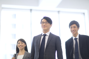 オフィスビルのロビーで微笑むビジネス男女の写真素材 [FYI02971570]