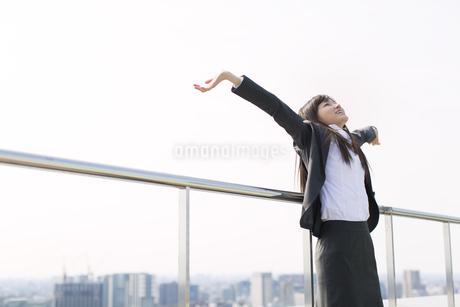 屋上で両手を上げるビジネス女性の写真素材 [FYI02971574]