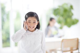スマートフォンで会話する女の子の写真素材 [FYI02971579]
