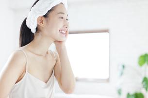 スキンケアをする微笑む女性の横顔の写真素材 [FYI02971580]