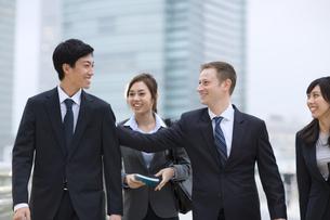 オフィスビルを背景に笑いながら歩くビジネス男女の写真素材 [FYI02971581]