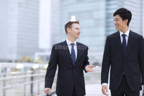 オフィスビルを背景に歩きながら話すビジネス男性2人の写真素材 [FYI02971582]