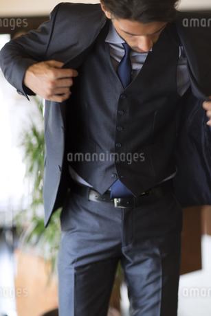 オフィスでスーツのジャケットを羽織るビジネス男性の写真素材 [FYI02971592]