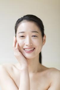 頬に片手を添えて微笑む女性の写真素材 [FYI02971596]