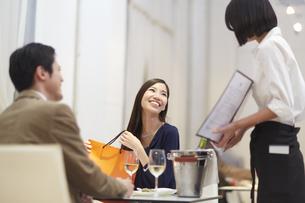 レストランで笑いながら店員と話すカップルの写真素材 [FYI02971602]