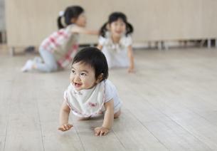 はいはいをして笑う赤ちゃんと2人の女の子の写真素材 [FYI02971604]