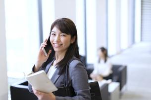 スマートフォンで通話するビジネス女性の写真素材 [FYI02971606]
