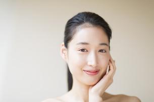 頬に片手を添えて微笑む女性の写真素材 [FYI02971607]