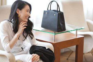 ソファーに座って微笑む女性の横顔の写真素材 [FYI02971610]