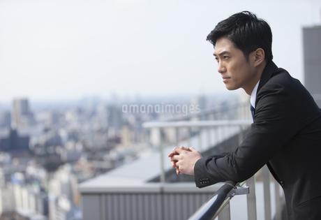 屋上で景色を眺めるビジネス男性の写真素材 [FYI02971611]