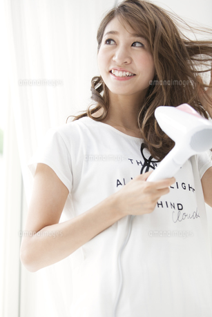 ドライヤーで髪を乾かす女性の写真素材 [FYI02971616]
