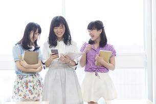 教室の窓際で教材を持って会話する女子学生たちの写真素材 [FYI02971617]