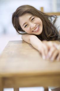 机に伏せてリラックスをする笑顔の女性の写真素材 [FYI02971620]