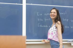 黒板の前で笑顔で振り向く女子学生の写真素材 [FYI02971621]