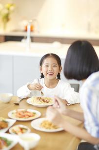 食事をしながら笑う女の子の写真素材 [FYI02971622]