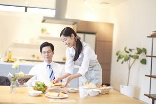 出勤前の朝食を運ぶ奥さんと食べる準備をする夫の写真素材 [FYI02971625]