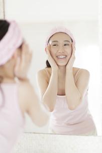鏡の前でスキンケアをする微笑む女性の写真素材 [FYI02971628]