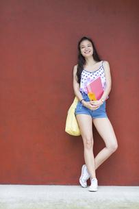 赤い壁の前で微笑む女子学生のポートレートの写真素材 [FYI02971630]