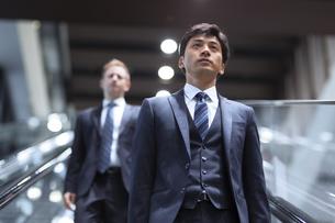 エスカレーターを降りるビジネス男性の写真素材 [FYI02971632]
